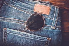 Okulary przeciwsłoneczni na cajgowych spodń rocznika retro stylu Obrazy Stock