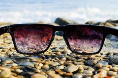 Okulary przeciwsłoneczni przy dennym tłem Zdjęcie Royalty Free