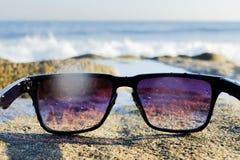 Okulary przeciwsłoneczni przy dennym tłem Obraz Royalty Free