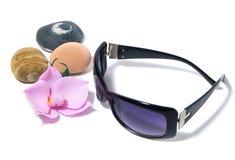 Okulary przeciwsłoneczni, purpurowi obiektywy, orchidea i morze kamienie, obraz royalty free