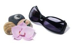 Okulary przeciwsłoneczni, purpurowi obiektywy, orchidea i morze kamienie, fotografia stock