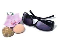 Okulary przeciwsłoneczni, purpurowi obiektywy, orchidea i morze kamienie, obraz stock