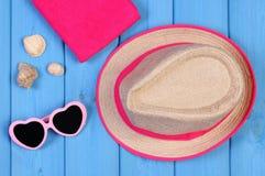 Okulary przeciwsłoneczni, słomiany kapelusz i ręcznik na błękitnych deskach, akcesoria dla lata zdjęcia royalty free