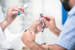 Okulista oferuje szkła klient dla badać i próbować Oko lekarka pokazuje cierpliwych obiektywy w widowisko sklepie fotografia royalty free