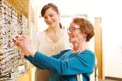 Okulista pomaga starej damy z szkłami Fotografia Stock