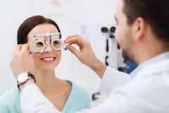 Okulista z próba pacjentem przy kliniką i ramą obraz royalty free
