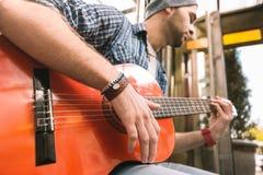 Okulizowanie męski gitarzysta wylicza żądła na gitarze zdjęcia stock