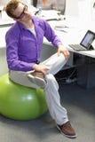 Okupacyjnej choroby zapobieganie - mężczyzna na stabilności piłce ma przerwę dla ćwiczenia Zdjęcia Royalty Free