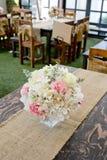 Okwitnięcie róża umieszczająca na biurku wewnątrz je obiad pokój Zdjęcia Royalty Free