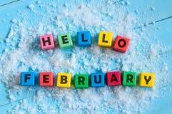 Olá! fevereiro escrito em cubos de madeira do brinquedo da cor no fundo claro com neve Fotos de Stock Royalty Free