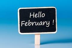 Olá! fevereiro - mensagem em pouco etiqueta de madeira no fundo azul 1º de fevereiro Fotografia de Stock Royalty Free