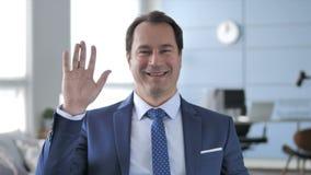 Olá!, homem de negócios envelhecido médio Waving Hand a dar boas-vindas video estoque