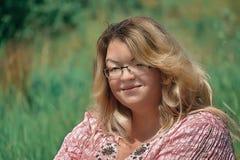 Olá!, o sol! Uma mulher gorda nova com cabelo luxúria e vidros senta-se em uma clareira ensolarado e em squintes Fotografia de Stock