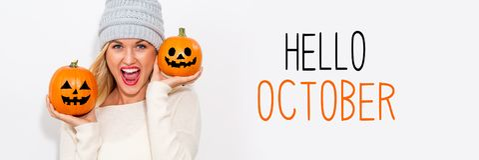 Olá! outubro com a mulher que guarda abóboras fotografia de stock royalty free