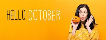 Olá! outubro com a mulher que guarda uma abóbora fotos de stock royalty free