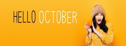 Olá! outubro com a mulher que guarda uma abóbora foto de stock