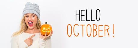 Olá! outubro com a mulher que guarda uma abóbora imagens de stock royalty free