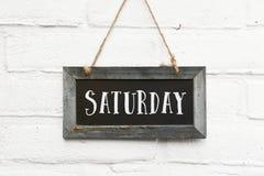 Olá! texto de sábado na parede exterior de suspensão do tijolo branco da placa foto de stock