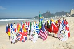 Olímpico e International señala la playa Río de Ipanema por medio de una bandera Foto de archivo libre de regalías