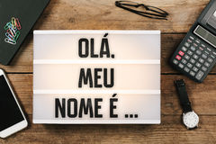 Ola, meu nome e ..., Portuguese text for Hello, My Name is. Ola, meu nome e, Portuguese text for Hello, My Name is, vintage style light box on office desktop royalty free stock photography