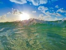 Ola oceánica con Sun, el cielo azul y las nubes foto de archivo libre de regalías