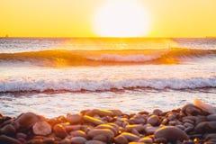 Ola oceánica que se estrella en la puesta del sol Fotos de archivo