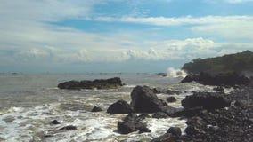 Ola oceánica que se estrella en Rocky Beach Coastline Roca en la costa de la playa de Loji en Ciletuh metrajes