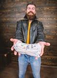 Olaglig vinst och svart kassa Grabbmaffiaåterförsäljare med kassavinst Brutal skäggig hipster för man att bära läderomslaget och royaltyfria bilder