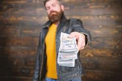 Olaglig vinst och svart kassa Grabbmaffiaåterförsäljare med kassavinst Mannen ger kassapengarmutan Rikedom och wellbeing royaltyfri fotografi