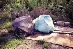 Olagligt dumpa i naturen; avskrädepåsar som lämnas i naturen - tonad bild royaltyfri bild