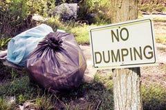Olagligt dumpa i naturen med inget dumpa tecken som indikerar i bygden - begreppsbild royaltyfri bild
