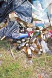 Olagligt dumpa med ?vergav flaskor, askar och plastp?sar i natur royaltyfri bild