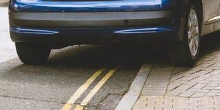 Olagligt parkerad bil p? dubbla gula linjer royaltyfri foto
