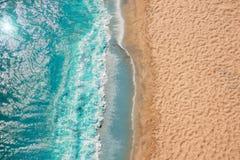 Olas oceánicas de la playa de la costa costa con espuma en la arena Visión superior desde el abejón fotos de archivo