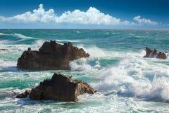 Olas oceánicas hermosas de la turquesa, costa costa de las rocas y cielo azul Imagen de archivo