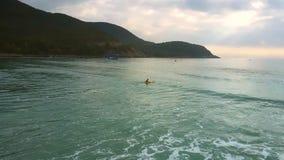 Olas oceánicas largas anchas de la visión aérea y persona que practica surf distante almacen de metraje de vídeo