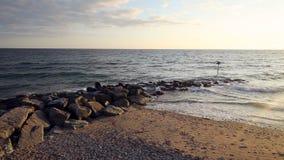 Olas oceánicas que machacan contra el rompeolas pedregoso metrajes