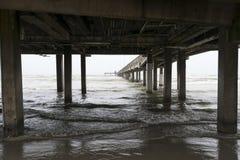 Olas oceánicas que ruedan sobre la playa debajo de un embarcadero largo Imágenes de archivo libres de regalías
