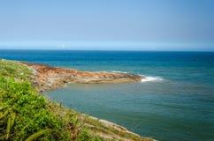 Olas oceánicas que se estrellan el día soleado en piedras Fotos de archivo