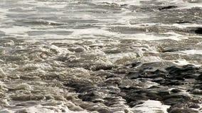 Olas oceánicas que se lavan para arriba en orilla de la roca y del fango almacen de metraje de vídeo