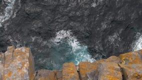 Olas oceánicas y acantilados rocosos anaranjados, visión superior, inclinación almacen de metraje de vídeo