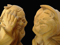 Old. Two wooden statues of elderly stock photography