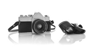 Old 35mm film photo camera. On white background with 35mm film strip royalty free stock image