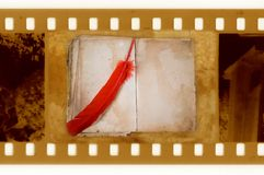 Old 35mm frame photo with vintage book and feather Royalty Free Stock Photography