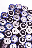Old AA batteries in a row, background Royalty Free Stock Images