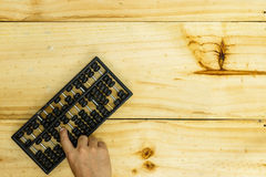 Old abacus and hand doing on wood Stock Photos