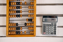 Old abacus and modern calculator royalty free stock images