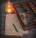 Old abacus, the paper with a pencil next to  lamp Stock Photos