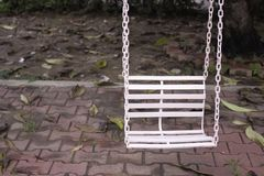 Old abandon white swing. In the garden Royalty Free Stock Images