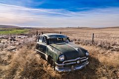 Abandoned antique car in field. Stock Image